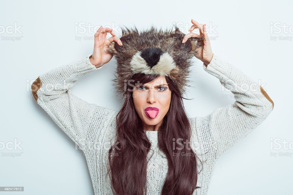 Carefree woman wearing fur cap and sticking out her tongue stock photo