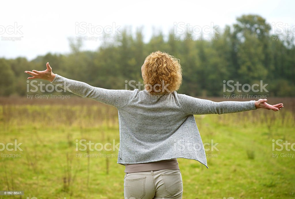 Carefree woman with arms spread open outdoors stock photo