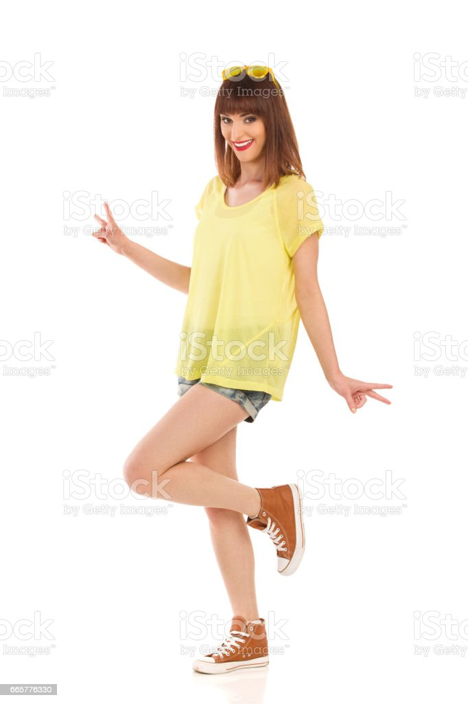 Carefree Young Girl Is Standing On One Leg And Smiling stock photo