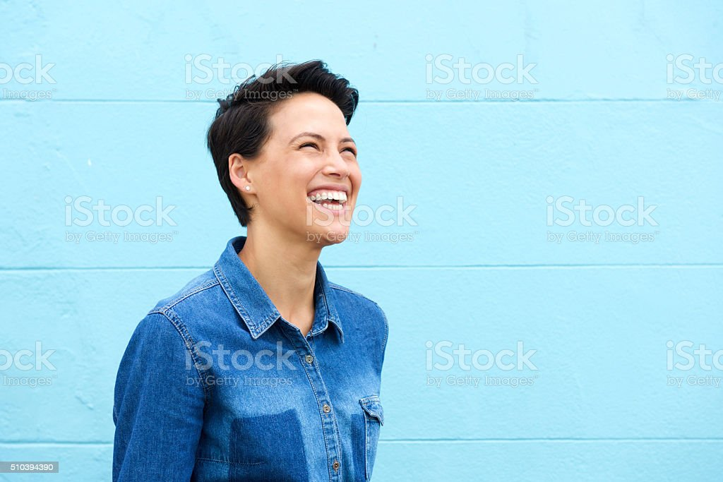 Carefree young woman laughing against blue background stock photo