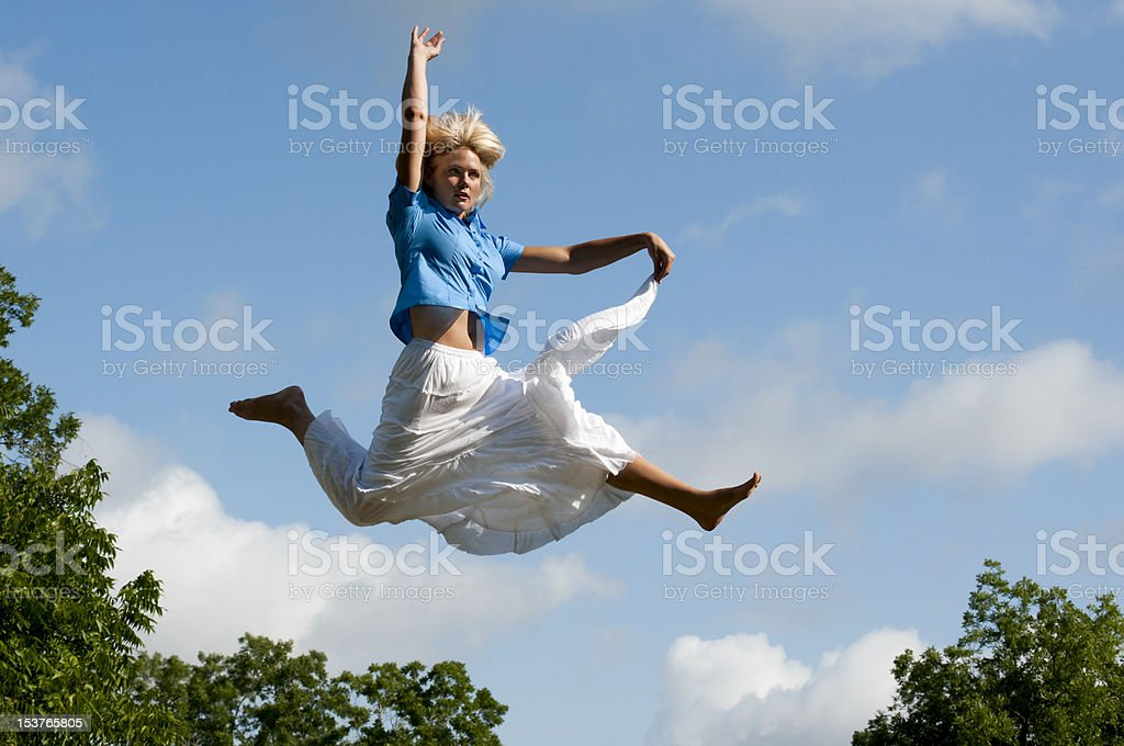 Carefree Young Woman Leaping for Joy Over Tree Tops stock photo
