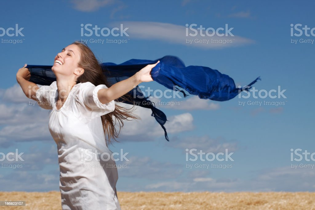Carefree Young Woman Outdoors Laughing into the Wind royalty-free stock photo