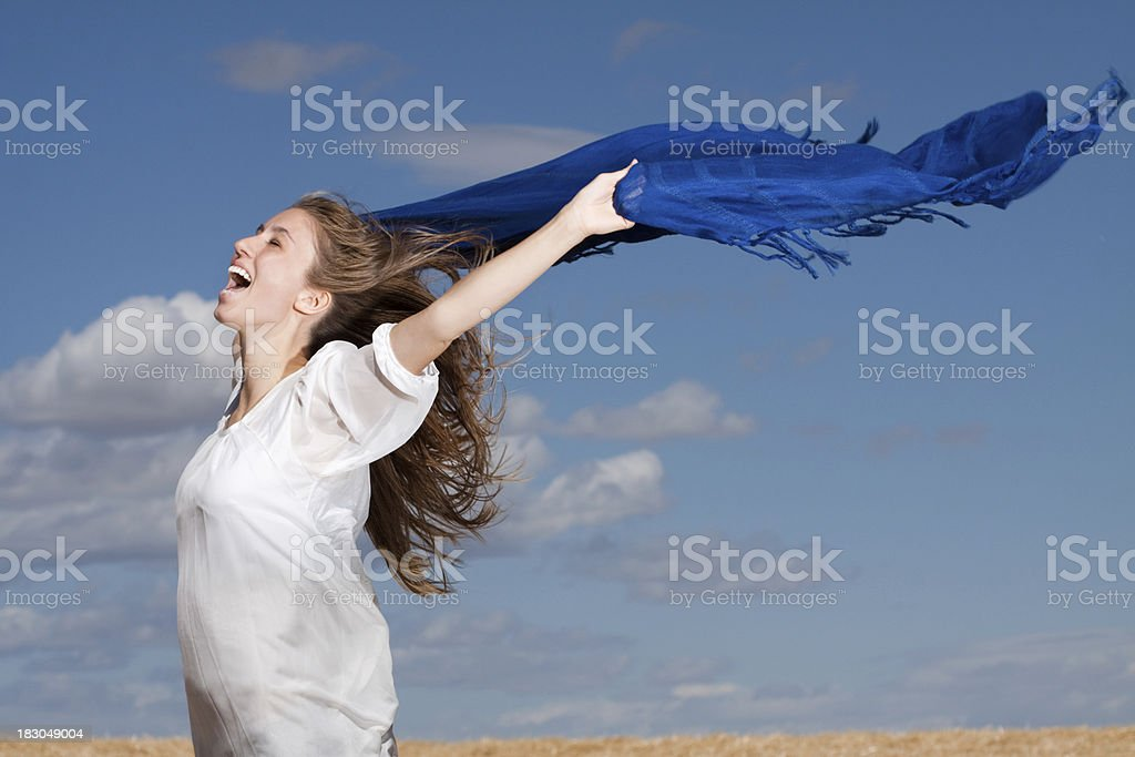 Carefree Young Woman Outdoors Shouting with Joy into the Wind royalty-free stock photo