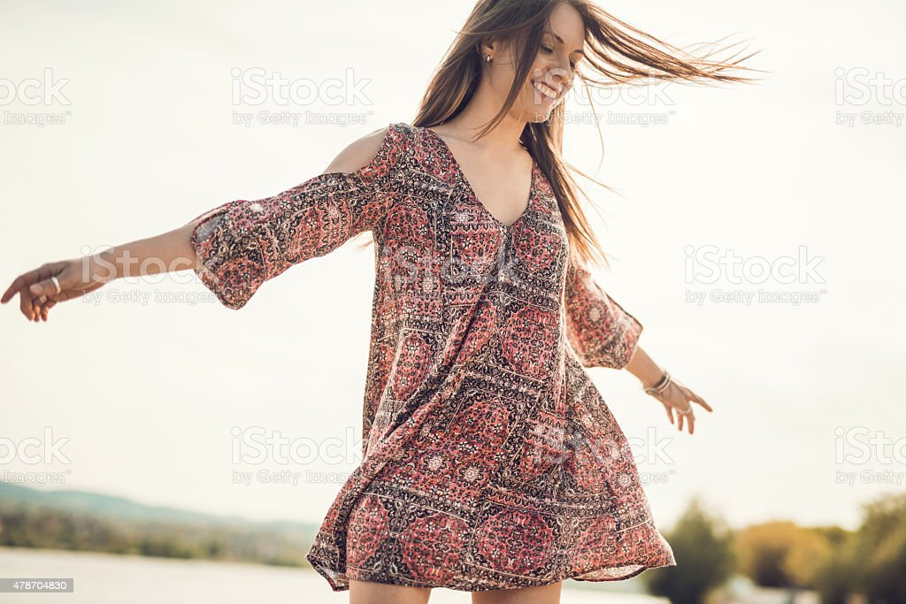 Carefree young woman spinning outdoors and having fun. stock photo