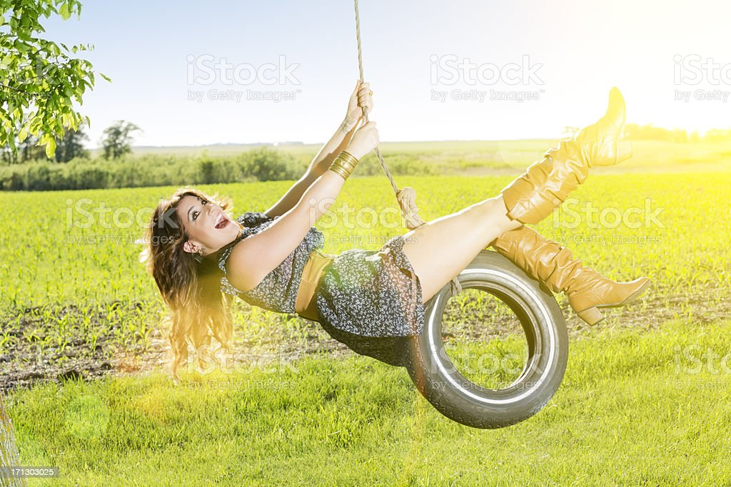 Carefree young woman swinging on a tire swing royalty-free stock photo