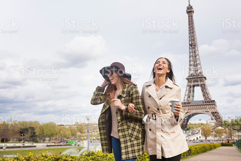 Carefree young women holding hands and having fun in Paris stock photo