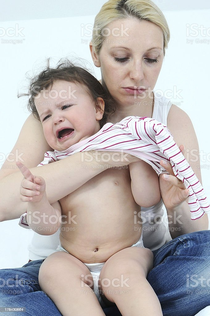 Careful mother getting dressed the crying daughter royalty-free stock photo