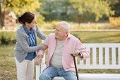 Caregiver and senior man in the park on park bench