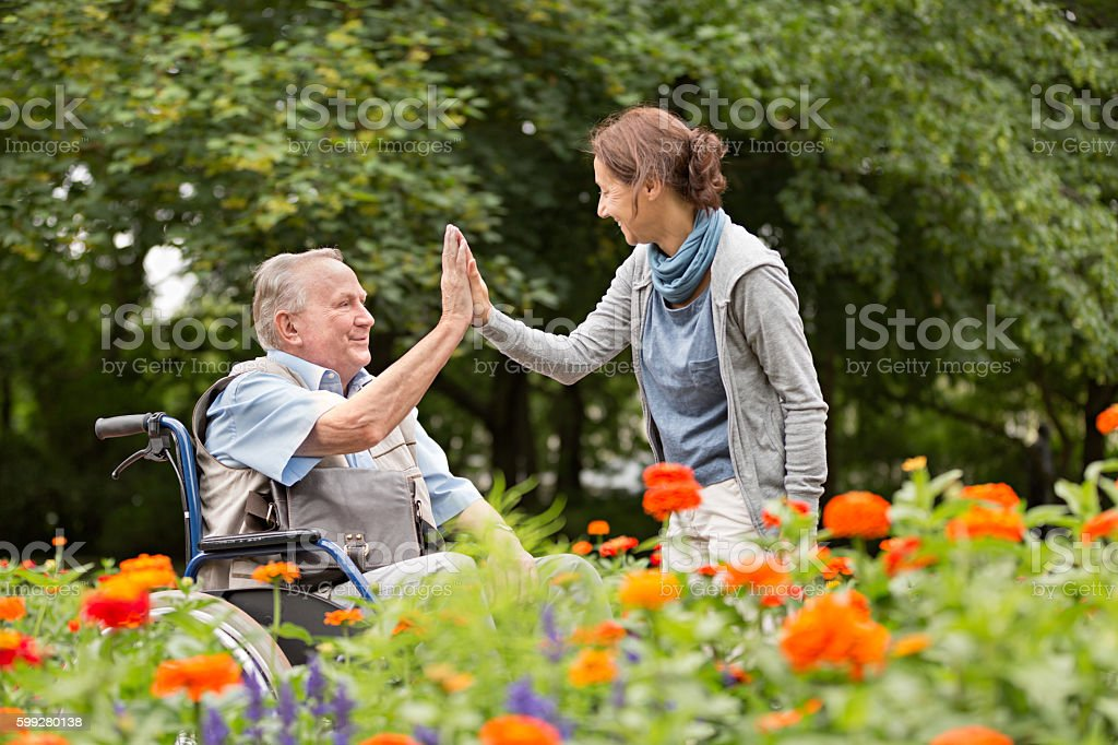 Caregiver and senior man on a wheelchair, walking in park stock photo