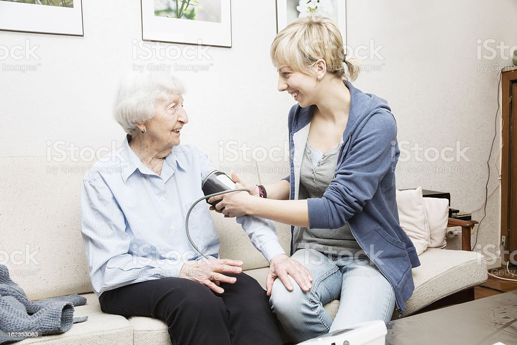 caregiver and senior woman taking blood pressure royalty-free stock photo
