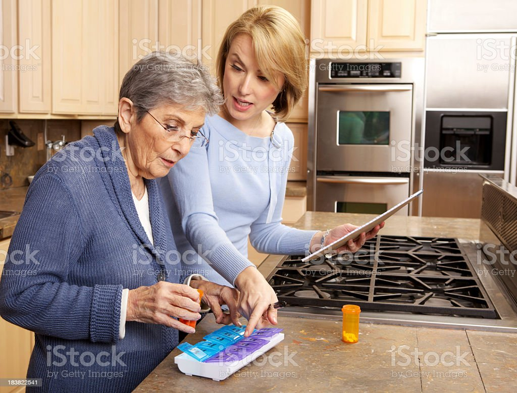 Caregiver assisting senior woman sort out her medication royalty-free stock photo
