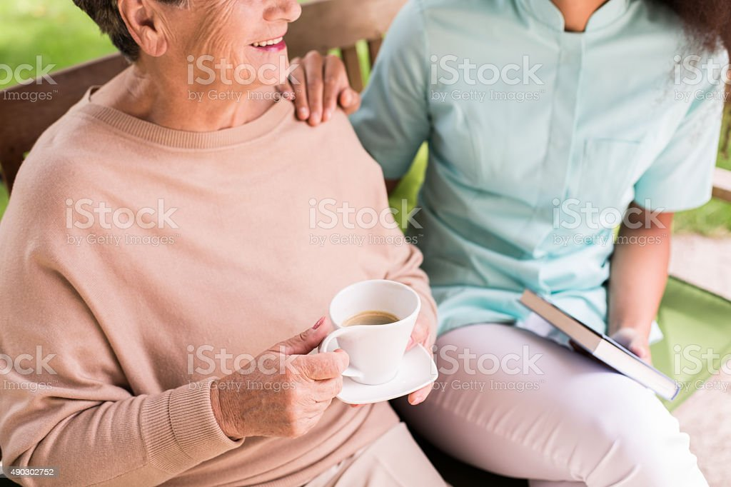 Caregiver caring about female pensioner stock photo
