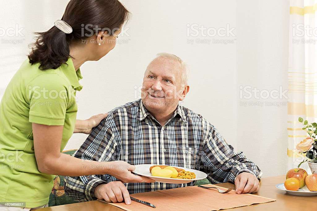 Caregiver giving senior man lunch in the kitchen royalty-free stock photo