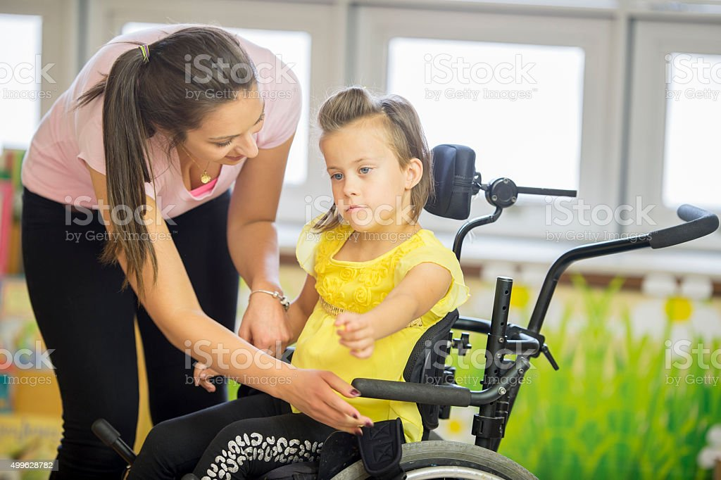 Caregiver Helping a Child Out of a Wheelchair stock photo