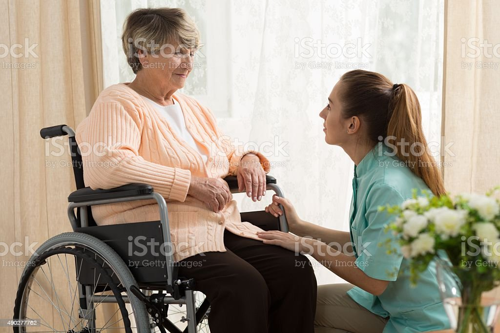 Caregiver helping old female stock photo