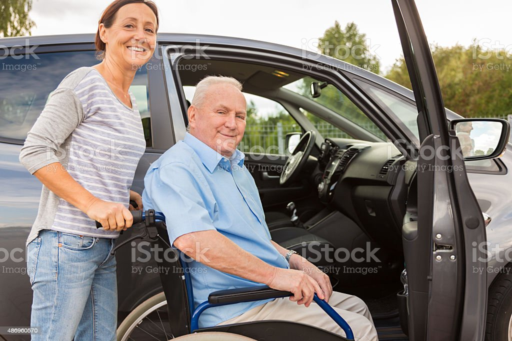 Caregiver helping senior into car stock photo