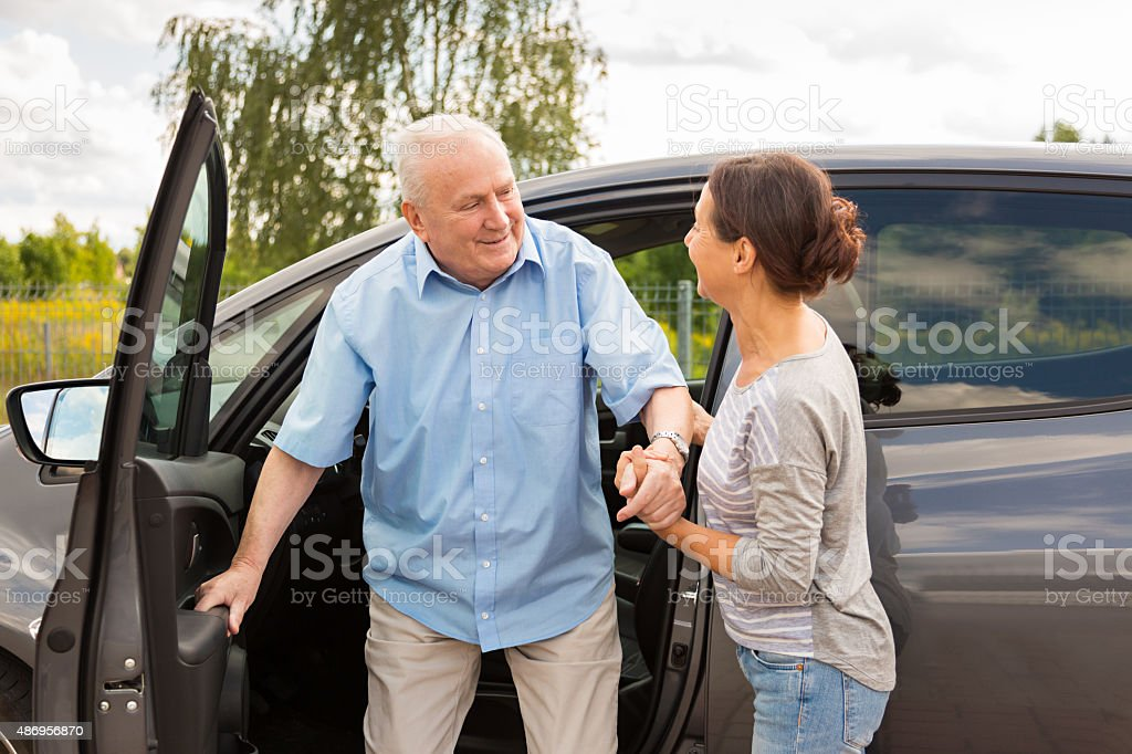 Caregiver helping senior out of the car stock photo