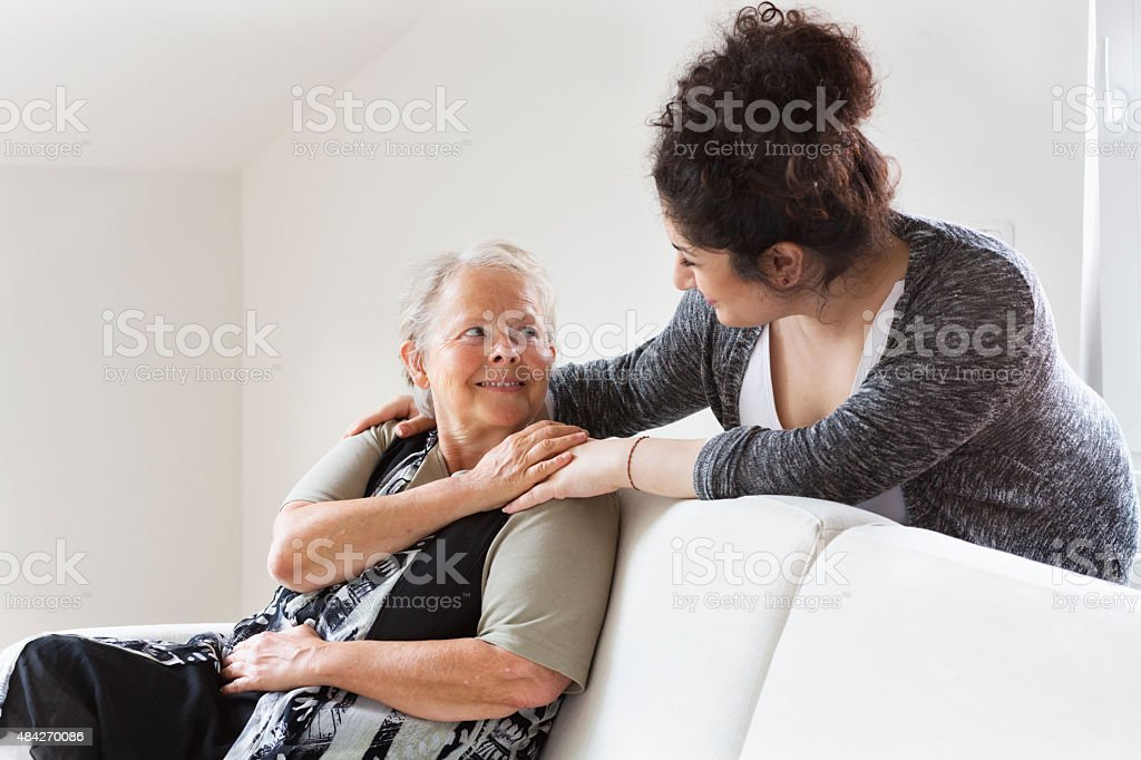 caregiver helping senior woman stock photo