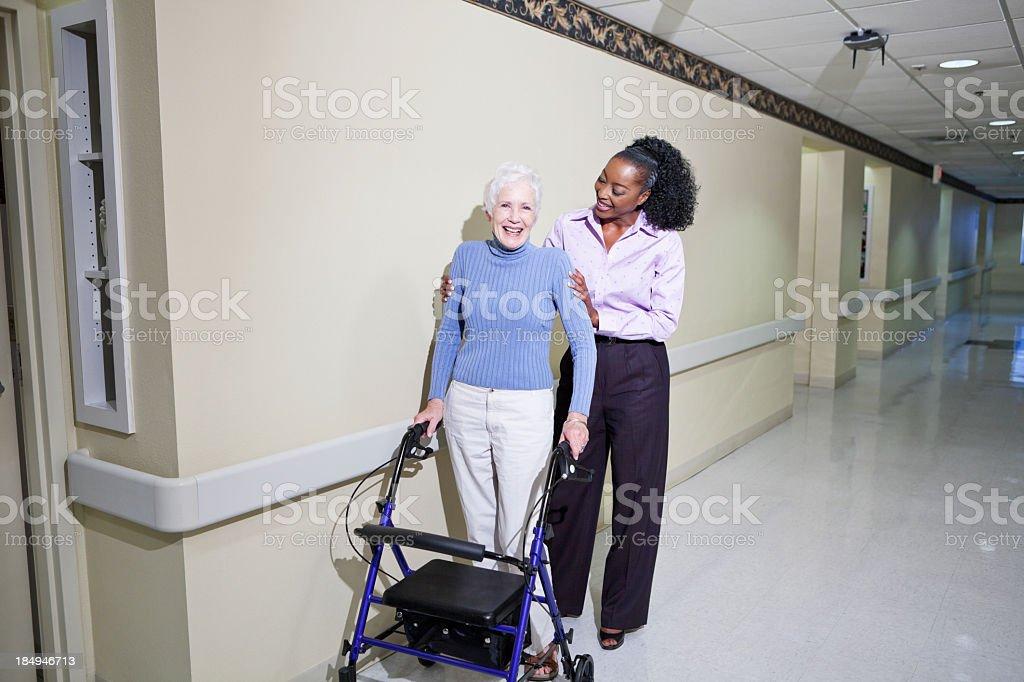 Caregiver helping senior woman walk down hallway stock photo