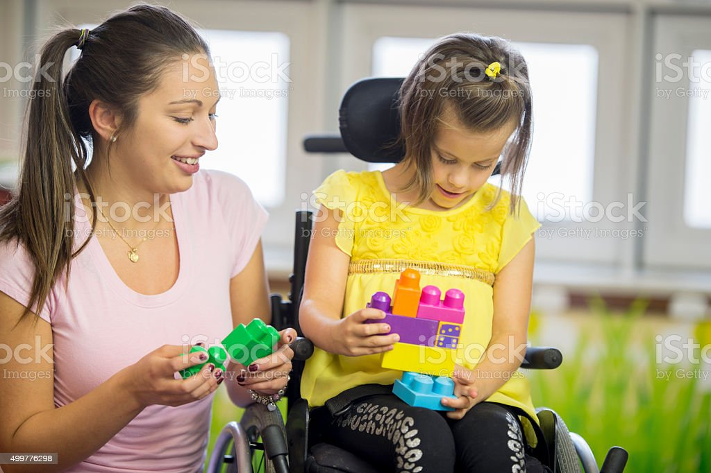 Caregiver is Helping a Disabled Girl Play with Blocks stock photo
