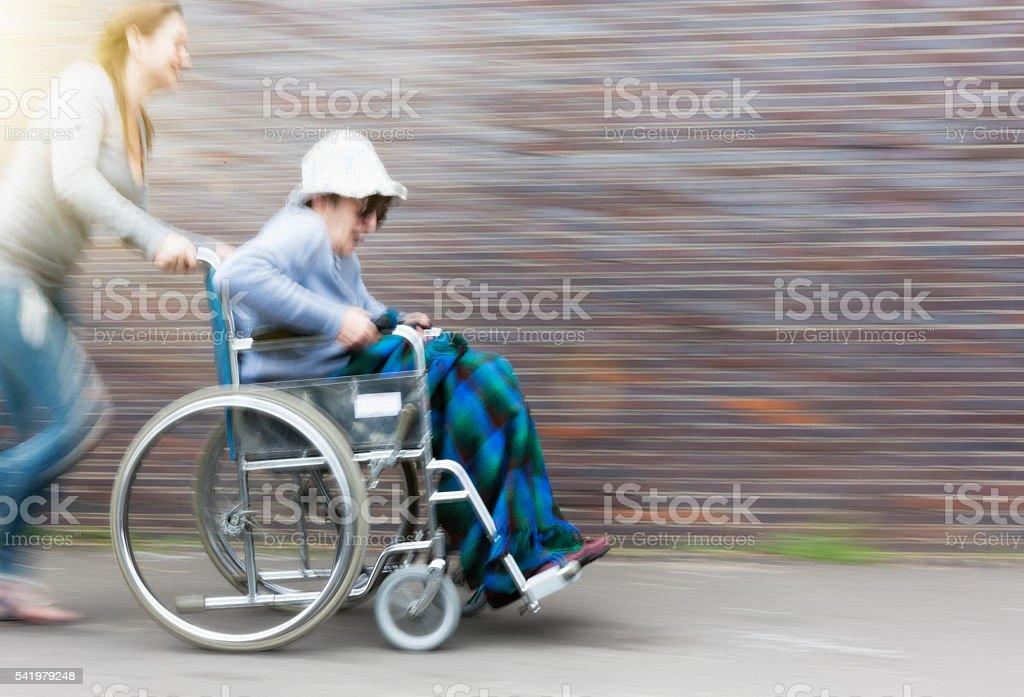 Caregiver pushes wheelchair senior at speed, both laughing stock photo