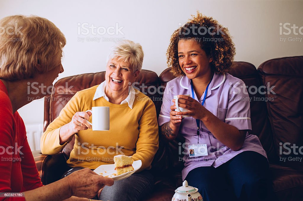 Caregiver Sharing Tea Time with her Patients stock photo