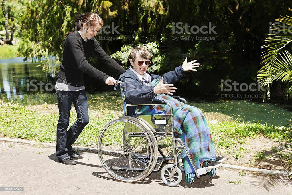 Caregiver smiles at grumpy gesticulating old woman in wheelchair royalty-free stock photo
