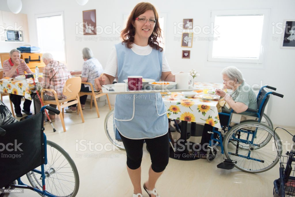 Caregiver Taking Lunch To A Senior Woman In The Room stock photo