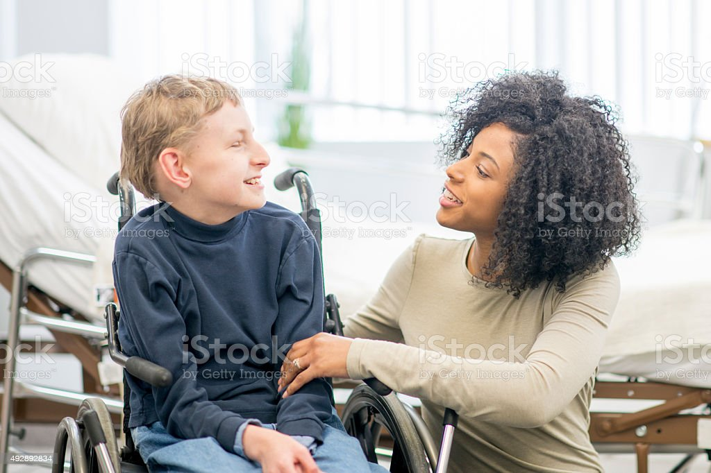 Caregiver Talking to Little Boy stock photo