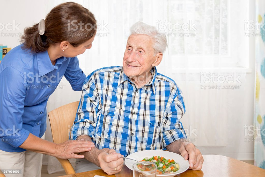 Caregiver with senior man, helping eating stock photo
