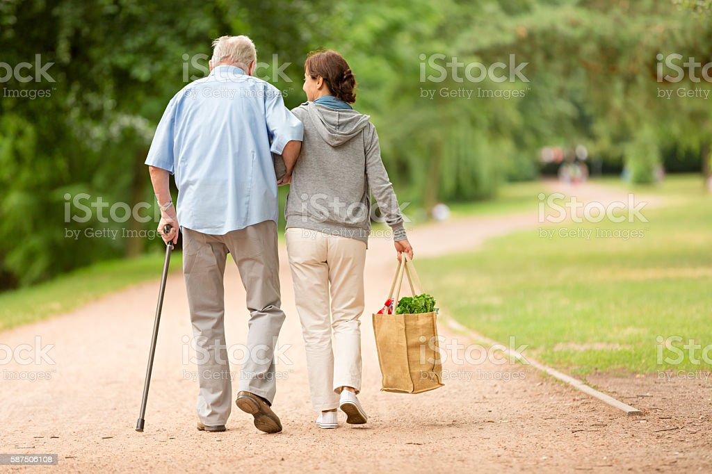 Caregiver – woman helping senior man with shopping stock photo