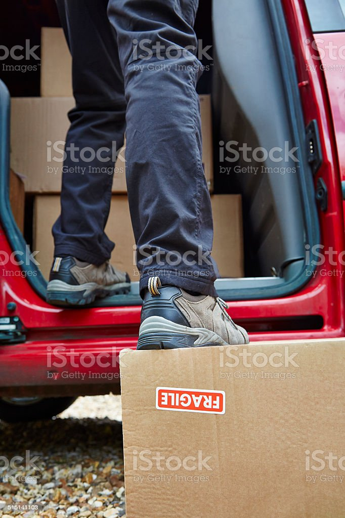 Careless Delivery Driver stands on upside down package stock photo