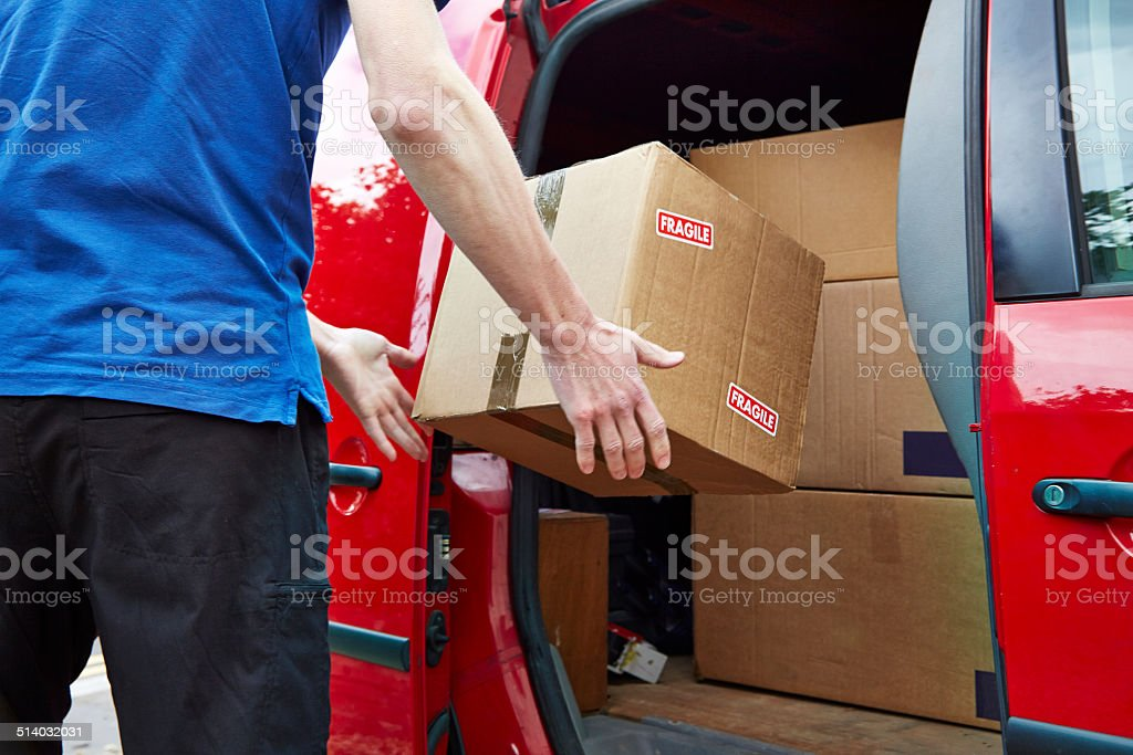 Careless delivery driver throws a package into van stock photo