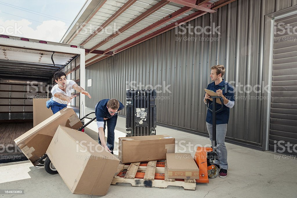 Careless Dock Workers Dropping Delivery Boxes While Loading Truck royalty-free stock photo
