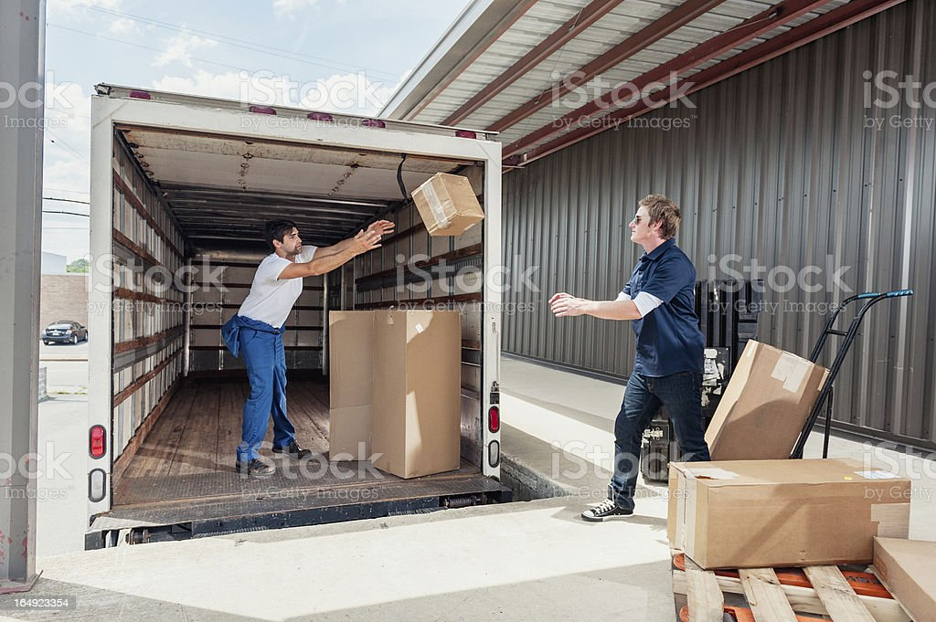 Careless Dock Workers Throwing Delivery Boxes While Unloading Truck royalty-free stock photo