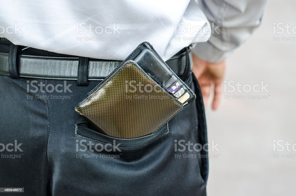 Careless man with wallet falling back pocket. Risk of theft. stock photo
