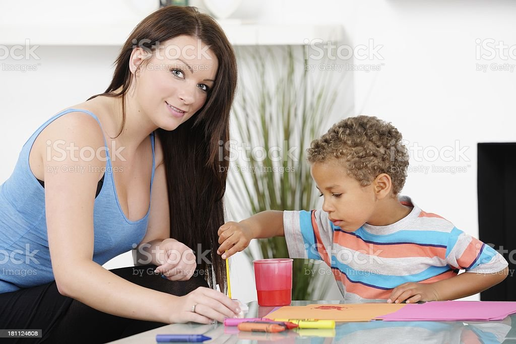 Carer Assisting Biracial Little Boy With Painting royalty-free stock photo