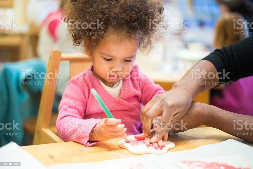 Carer Assisting Toddler To Do Imprint Of Her Hand stock photo