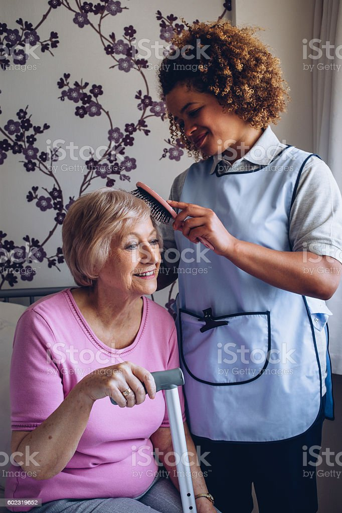 Carer Brushing Patients Hair stock photo