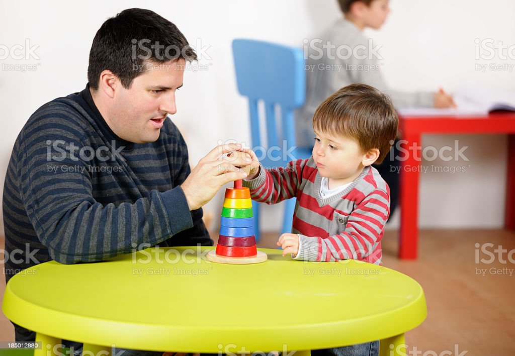 Carer/ Father Assisting Toddler During Playtime In A Nursery royalty-free stock photo