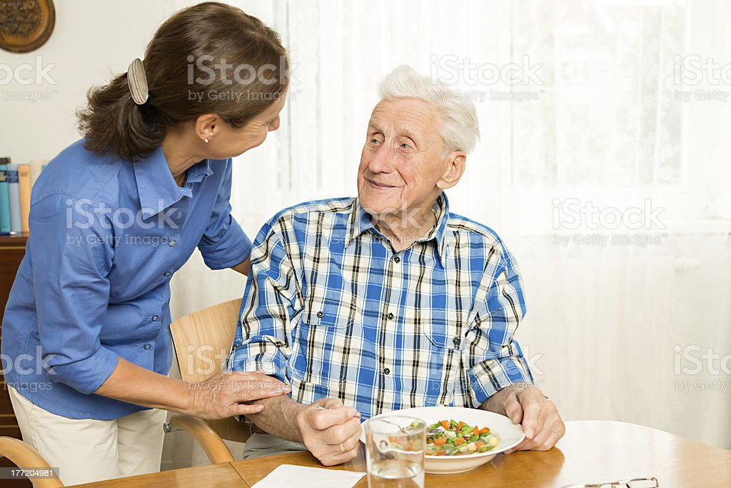 Carer giving senior man lunch royalty-free stock photo