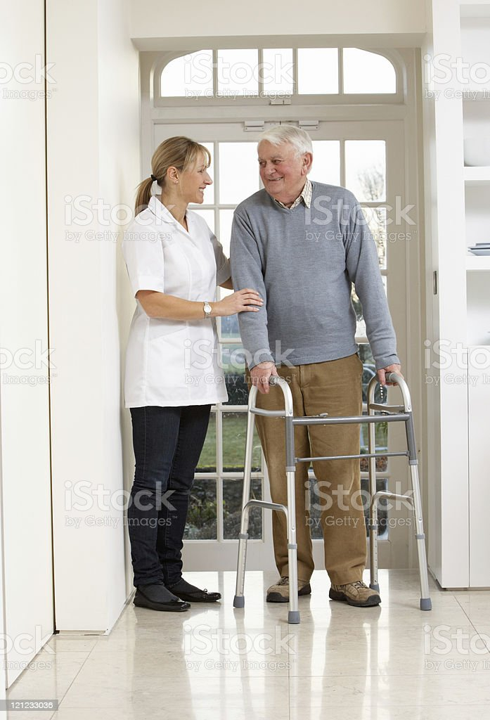 Carer Helping Elderly Senior Man Using Walking Frame stock photo