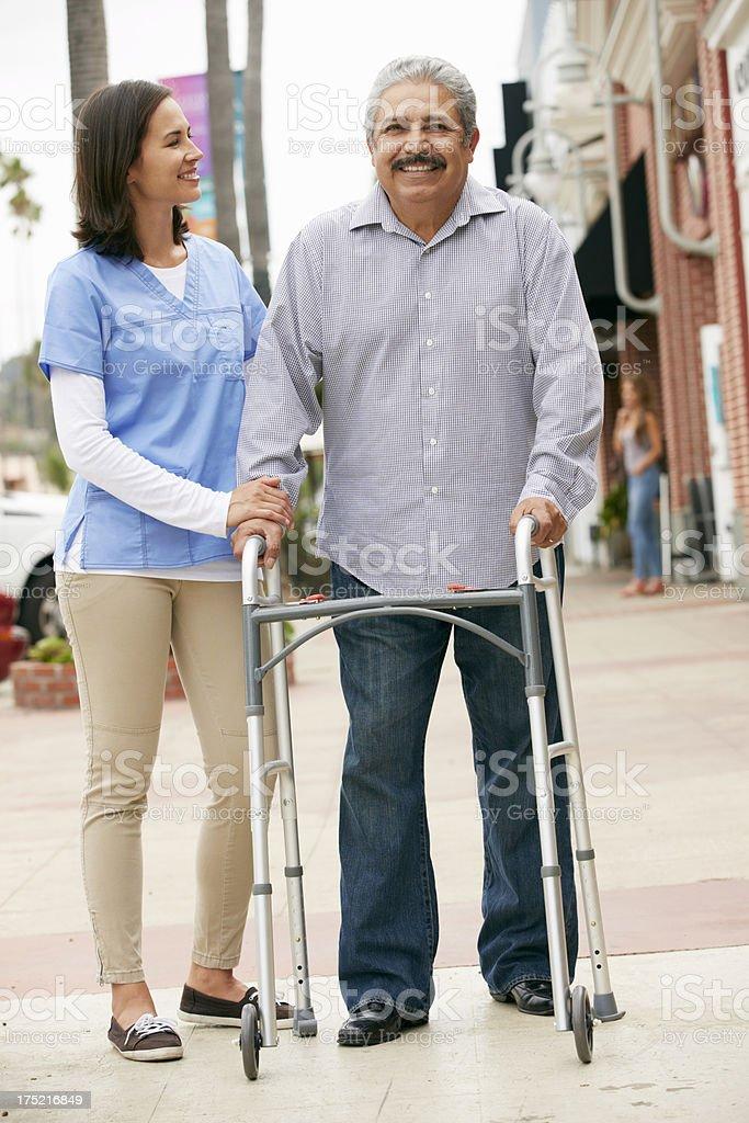 Carer Helping Senior Man To Use Walking Frame royalty-free stock photo
