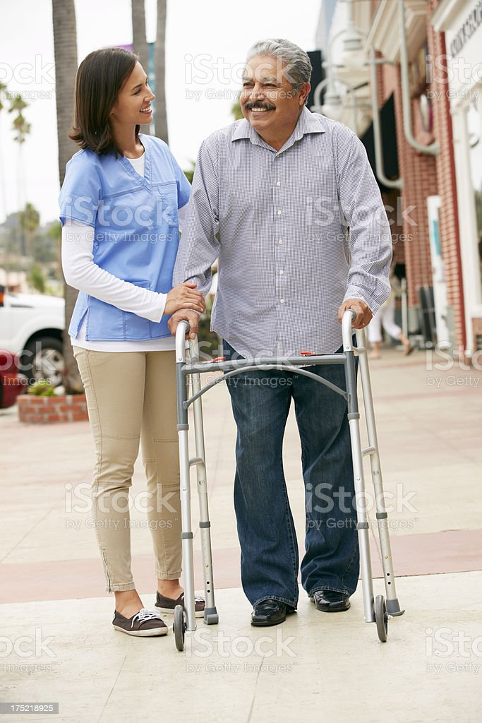 Carer Helping Senior Man To Use Walking Frame stock photo