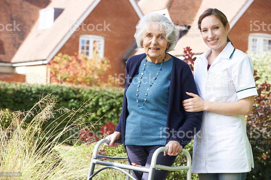 Carer Helping Senior Woman To Walk stock photo