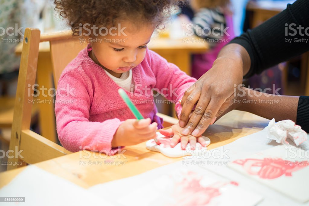 Carer Helping Toddler To Do Imprint Of Her Hand stock photo