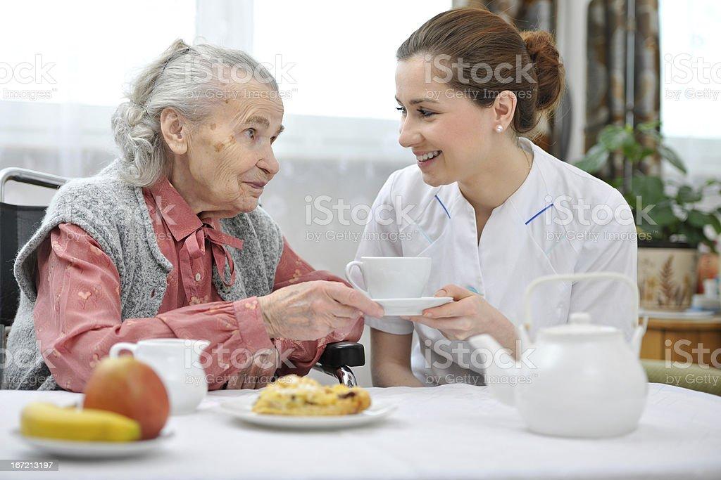 Carer in nursing home handing an elderly woman a cup of tea stock photo