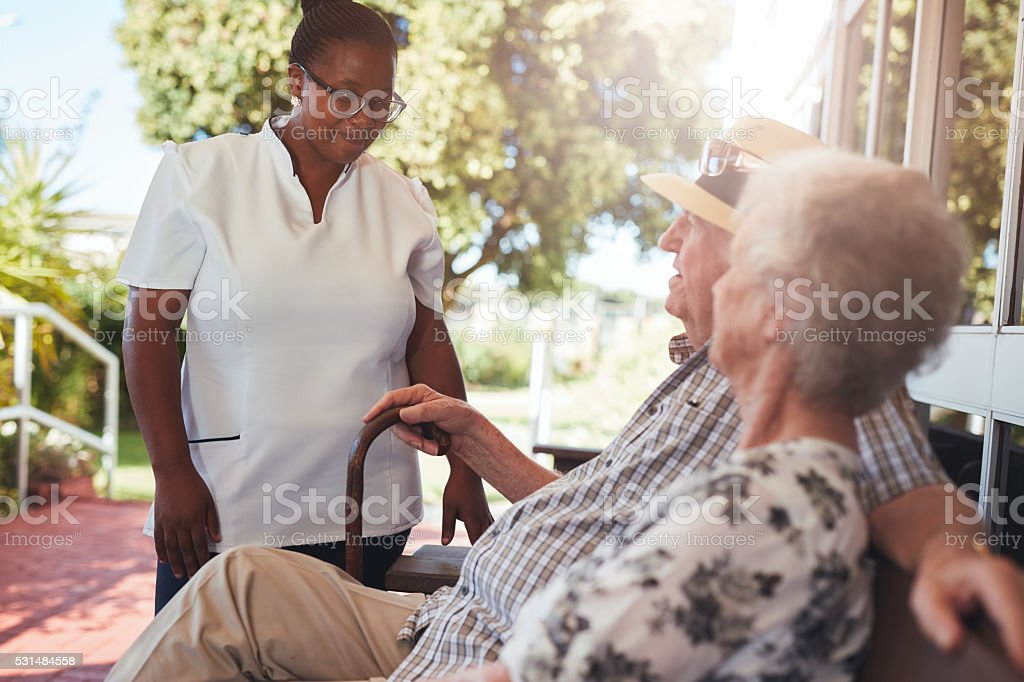 Carer looking after an elderly couple stock photo