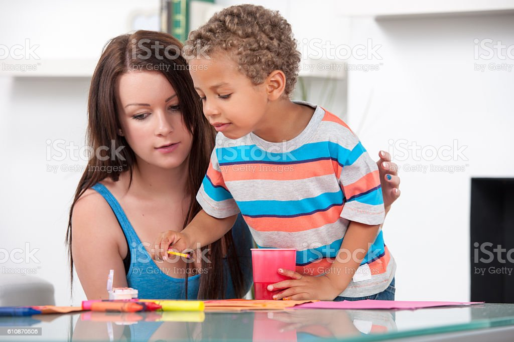 Carer/ Mother Supervising Biracial Little Boy With Painting stock photo