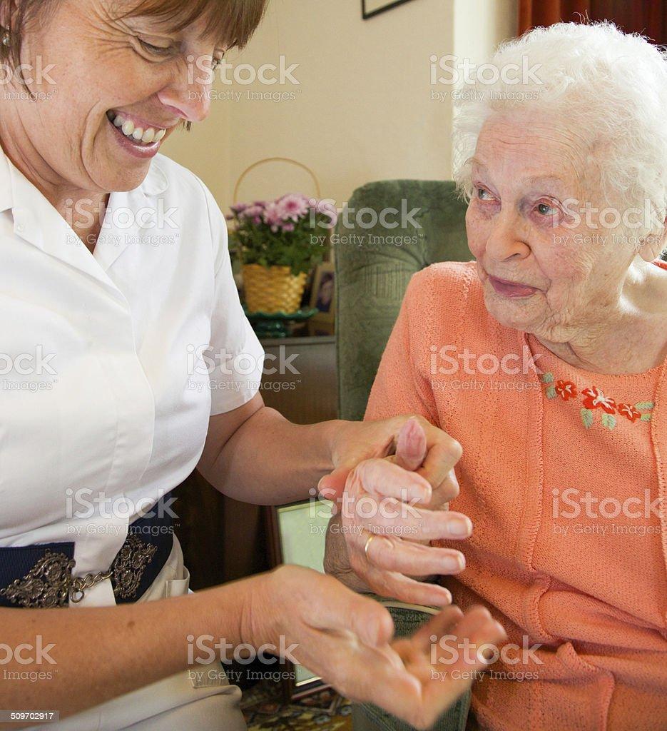 Carer nurse giving an elderly woman a hand massage stock photo
